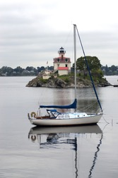 Sailboat near Pomham Rocks lighthouse on a rocky island on an  overcast day.