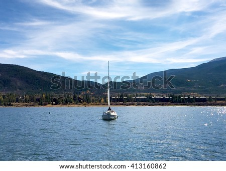 Sailboat on a lake in Frisco, Colorado with mountains and clear sky in the background