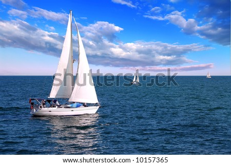 Sailboat sailing in the morning with blue cloudy sky