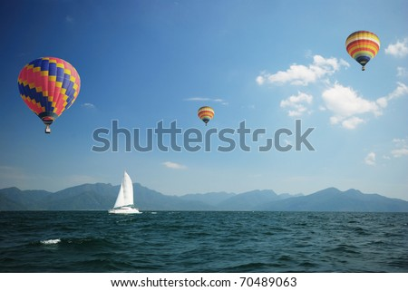 Sailboat sailing through the sea with colorful balloon high above
