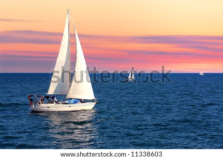 Sailboat sailing towards sunset on a calm evening