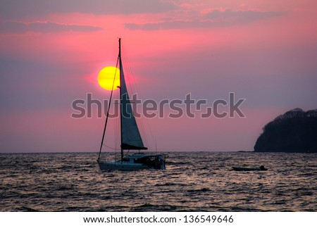 Sailboat Sunset Costa Rica. A lone sailboat against a sunset in the pacific ocean off the coast of Costa Rica.