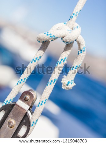 Sailboat winch with rope on yacht deck. Detail, low depth of focus. Leasure activities and extreme sport. Low depth of focus. #1315048703