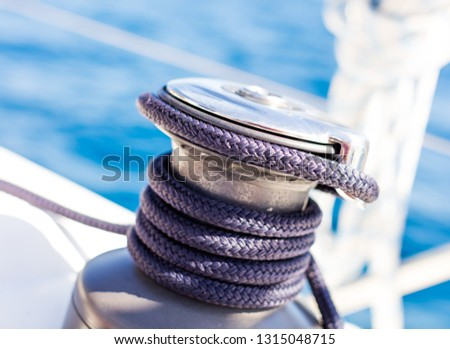 Sailboat winch with rope on yacht deck. Detail, low depth of focus. Leasure activities and extreme sport. Low depth of focus. #1315048715