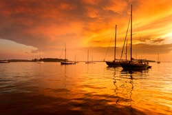 Sailboats and a beautiful red and orange sunset in Penobscot Bay in Maine