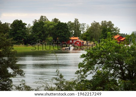 Sailboats and cutters moored to a pier. Traditional houses colored with falu red dye. Summer vacations, recreation, leisure activity, service, private vessels. Björkö island, lake Mälaren, Sweden Stock fotó ©