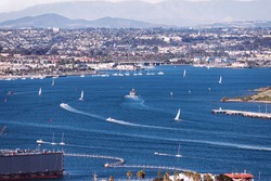 sailboats and harbor cruise ships leave their wakes on the west end of the San Diego Bay with the city and blurred mountains in the background