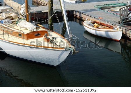 Sailboats and small skiff sitting in calm waters at a local new england dock