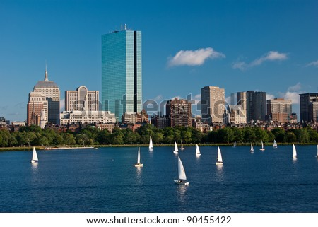 Sailboats are in the foreground of a view of Copley Square as seen from across the Charles River