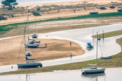 Sailboats at low tide in Bassin d'Arcachon in Cap Ferret, France.