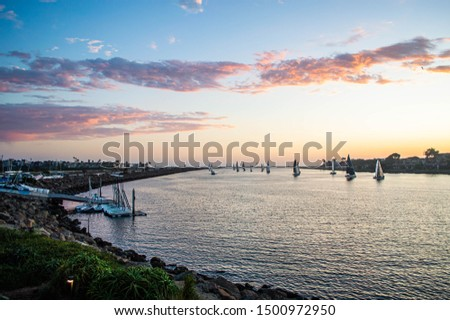 Sailboats enter the main channel to Marina del Rey, CA at sunset #1500972950