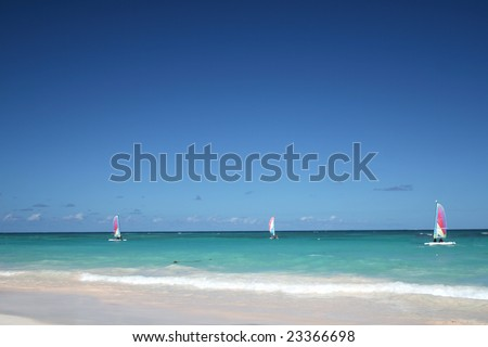 Sailboats in ocean - Beautiful Caribbean tropical beach with white sand and green waves. FOCUS on sailboats
