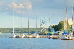 Sailboats moored to a pier in a yacht marina. Factory in the background. Balsta, Mälaren lake, Sweden. Industry, ecological issues, pollution, economic growth, transportation, leisure activity