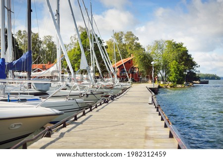 Sailboats moored to a pier. Traditional houses colored with falu red dye.  Björkö island, lake Mälaren, Sweden Stock fotó ©