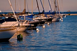 Sailboats rest peacefully at their moorings as the sun sets on Monroe Harbor, Chicago lakefront.