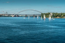 sailboats sail on the river. Panoramic view of the Dnieper. Competition sport of sailing.Yacht and beautiful riverscape.Sailboats floating on blue water.Recreational Water Sports, Extreme Sport Action