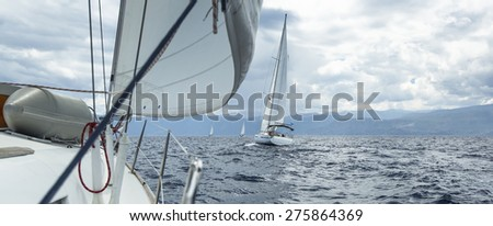 Sailboats sailing in regatta on the Mediterranean Sea in cloudy weather. Cruise Yachting.