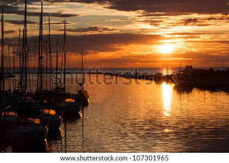 Sailboats silhouette in harbor with sunset and clouds - stock photo