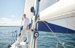 sailing, age, tourism, travel and people concept - happy senior man on sail boat or yacht floating in sea
