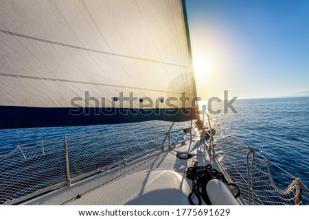 Sailing at calm weather with sun. A view from the yacht's deck to the bow and sails. Sail boat with set up sails gliding in open sea. Greece, Europe