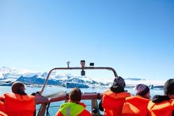 Sailing between icebergs in Jokulsarlon Lagoon, Iceland. Crowd on amphibian tour among melting glaciers.