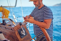 Sailing boat captain using smartphone for navigation on the open sea.
