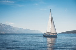 Sailing boat in the sea against the backdrop of mountains