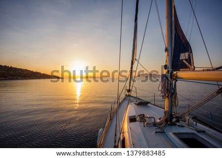 Sailing boat in the sea during awesome sunset. Luxury yacht and cruise holiday.