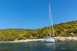 Sailing boat moored off the coast in Croatia. Sailboats moored in the bay. Yachting sport. Holiday on a sailboat.