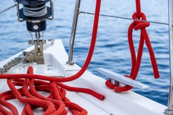Sailing boat mooring ropes on the deck. Red color yachting rope tied on cleat, cruise card template. Sailboat safety tools and equipment, closeup view