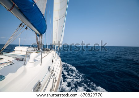 Sailing boat moves in the open sea under the sails. No land or islands on the horizon