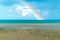 Sailing boat on the sea in the middle of a rainbow