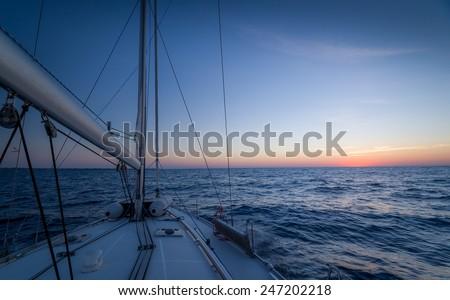 Sailing boat, open sea and sundown at the horizon