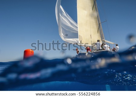 Sailing boat with spinnaker on windward mark - red buoy. Waterline view.  #556224856