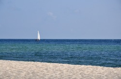 Sailing boat yacht alone lonely on calm clear baltic sea beach