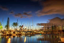 Sailing boats and yachts docked at the Ala Wai Harbor, the largest yacht harbor of Hawaii, reflecting in the sea. Honolulu harbor skyline by night, Oahu, Hawaii.