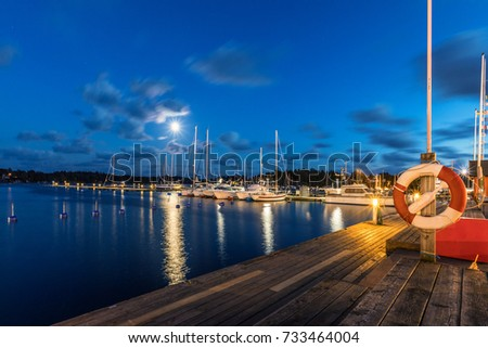 Sailing boats and yachts in marina at night with cloudy sky. Nynashamn. Sweden. #733464004