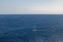 Sailing boats in distance in Aegean sea with stormy waves on blue water. Travel Greece, Mediterranean sea. Summer seascape