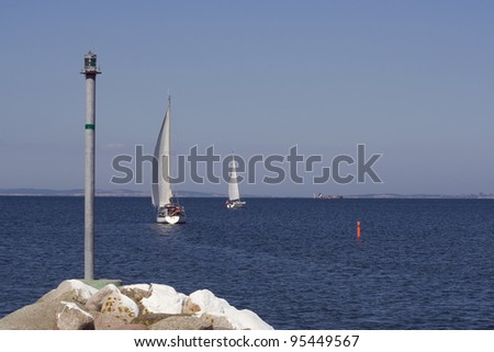 Sailing boats leaving the small harbour Norsminde, Denmark