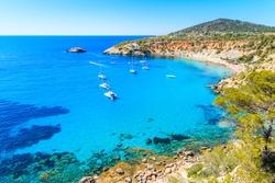 Sailing boats on Cala d'Hort bay with beautiful azure blue sea water, Ibiza island, Spain