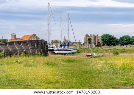 Sailing boats on dry land near a shed made from an upturned boat on the island of Lindisfarne Northumberland With Lindisfarne priory in the background