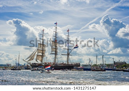 Sailing boats on river IJ during Sail Amsterdam (Sail In), Netherlands, with beautiful sky.