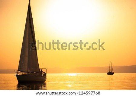 Sailing boats with a beautiful sunset at the sea