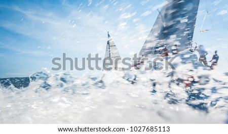 Sailing boats with spinnakers racing on open sea, water drift is motion blured
