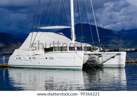 Sailing catamaran morred. Heavy sky background and reflections on water vivid image.