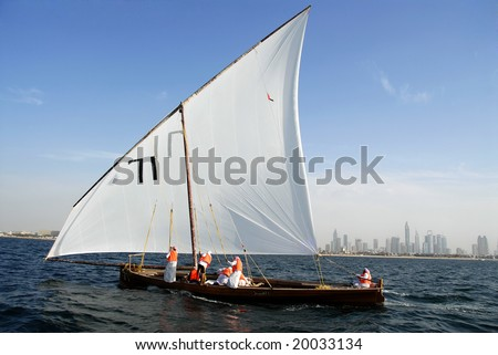 Sailing Dhow Against The Distant Cityscape Of Dubai