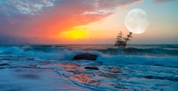 Sailing old ship in stormy sea in the background dramatic sunset and full moon