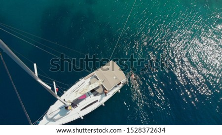 Sailing regatta, boat trip, top view. White yacht in the blue sea, drone photo. People relax on a yacht and dive into the water, sea voyage #1528372634