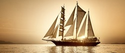 Sailing ship at sunset. Yacht cruises. Traveling and leisure under sail. Yachting. Travel