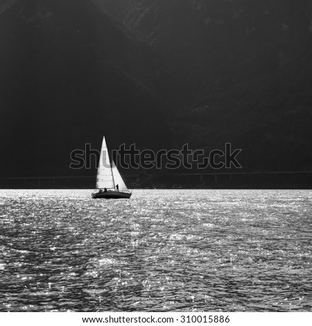 Sailing ship on the mountain lake. Sun reflected in water. Black and White